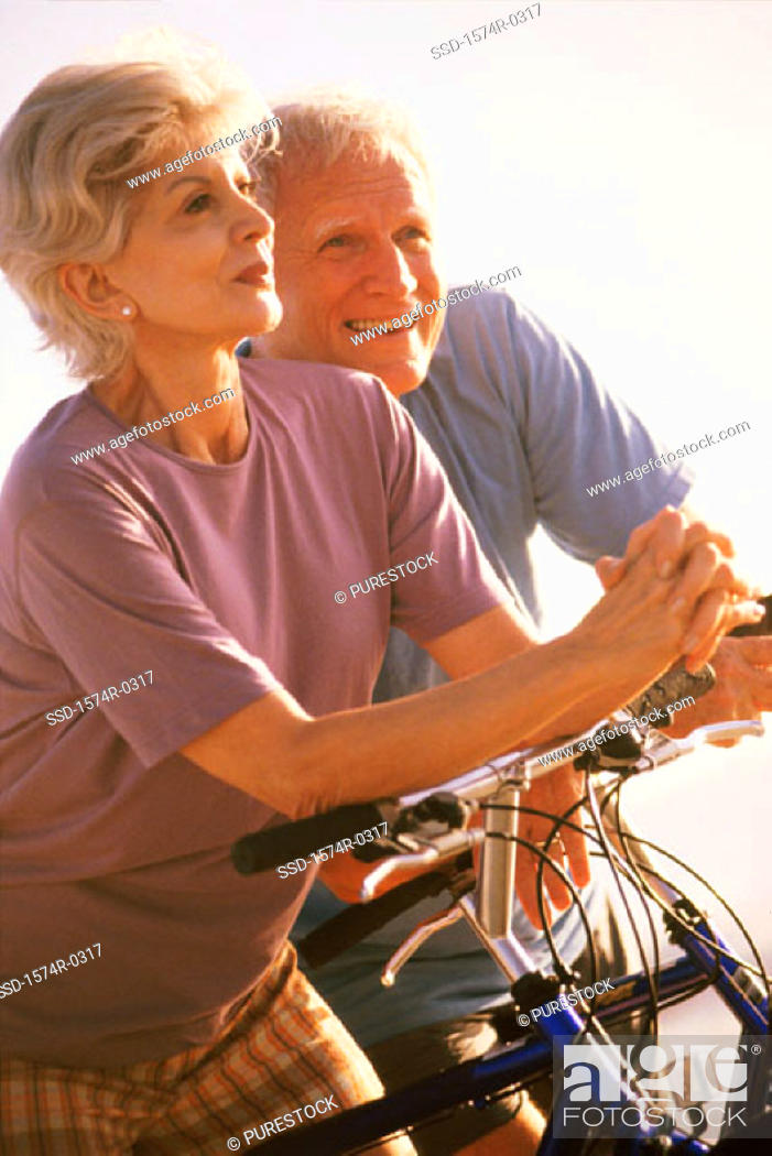 Stock Photo: Senior couple standing with bicycles.