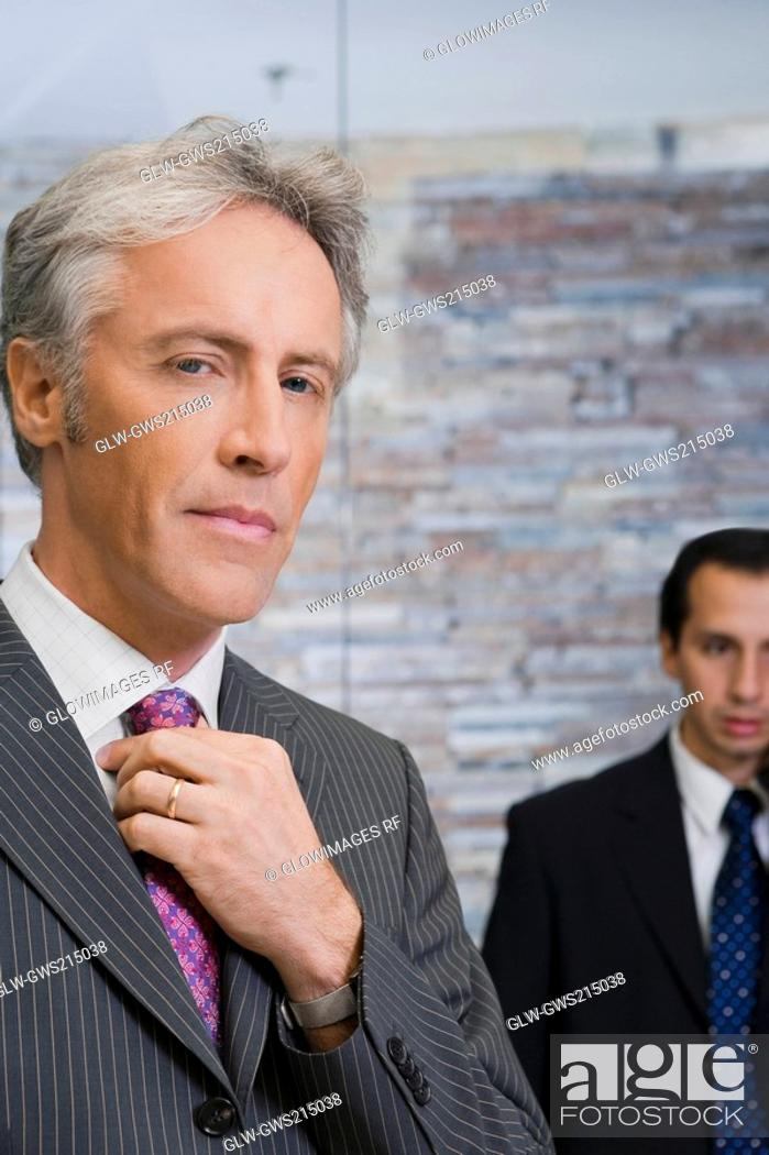 Stock Photo: Close-up of a mature man adjusting his tie.