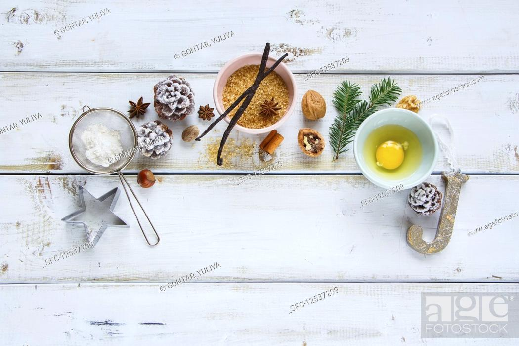 Stock Photo: Christmas baking frame made of sugar, egg, flour, larch branch, pine cones, vanilla sticks, anise star and nuts.
