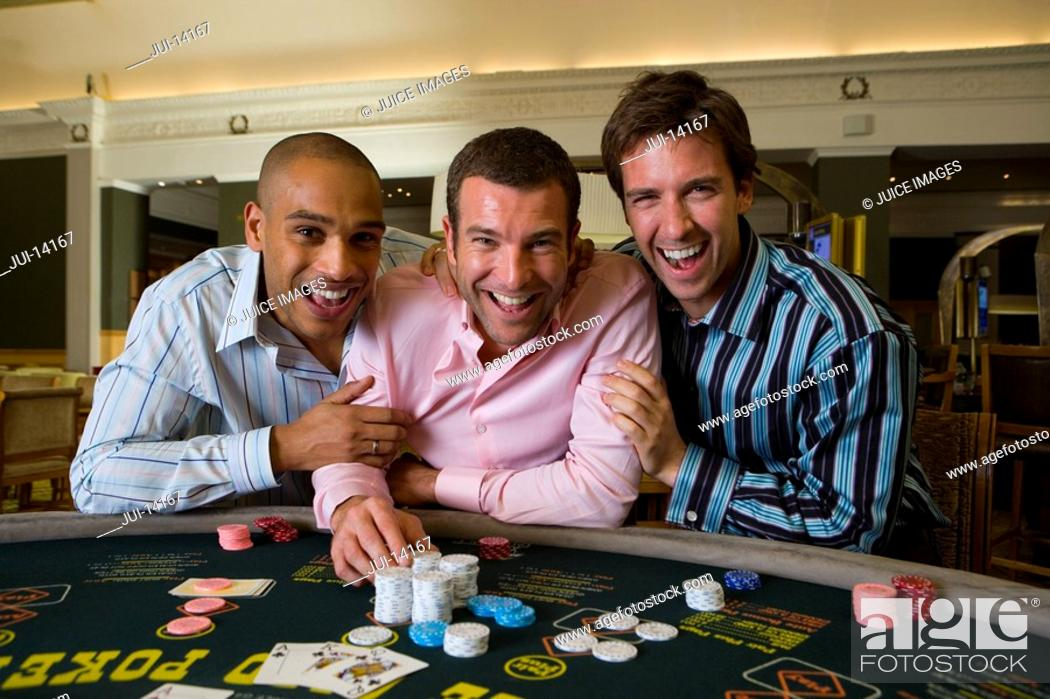 Stock Photo: Young man flanked by friends gambling at poker table in casino, smiling, portrait.