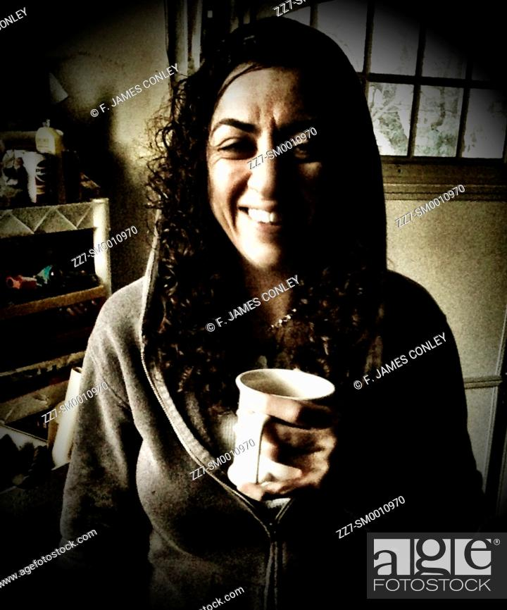Stock Photo: A woman enjoys a cup of coffee.