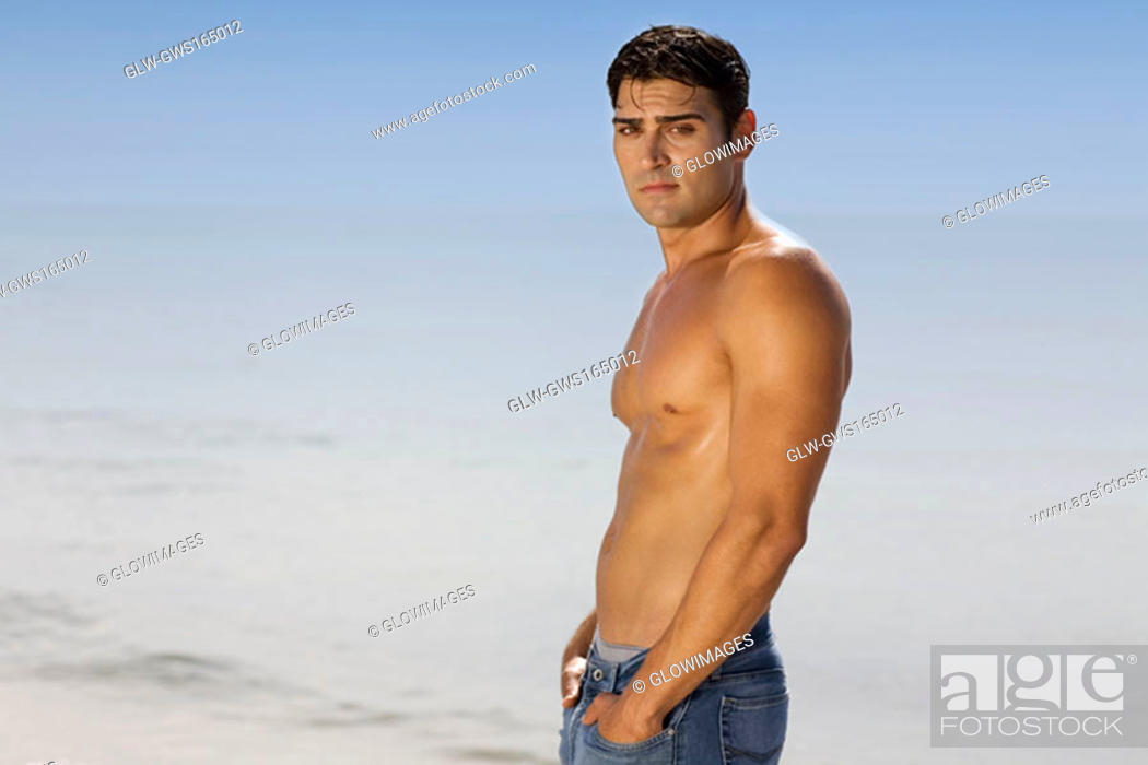 Stock Photo: Portrait of a mid adult man standing on the beach.