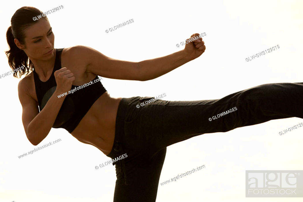 Stock Photo: Mid adult woman practicing martial arts.