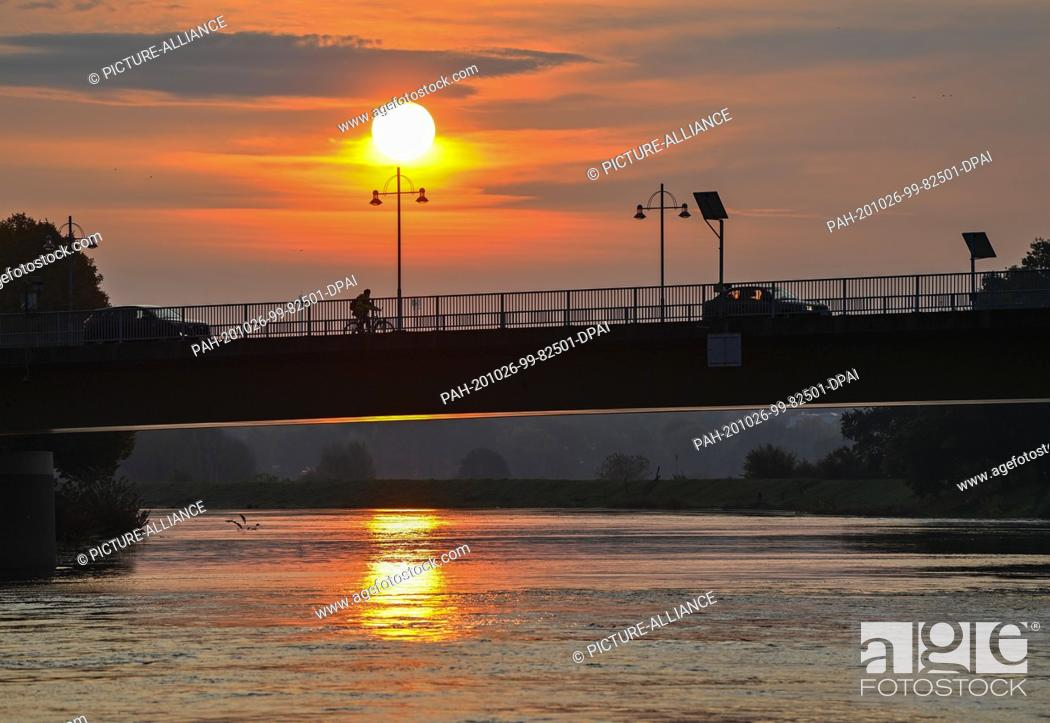 Stock Photo: 26 October 2020, Brandenburg, Frankfurt (Oder): The sunrise shines in the early morning at the border river Oder above the city bridge between the Polish.