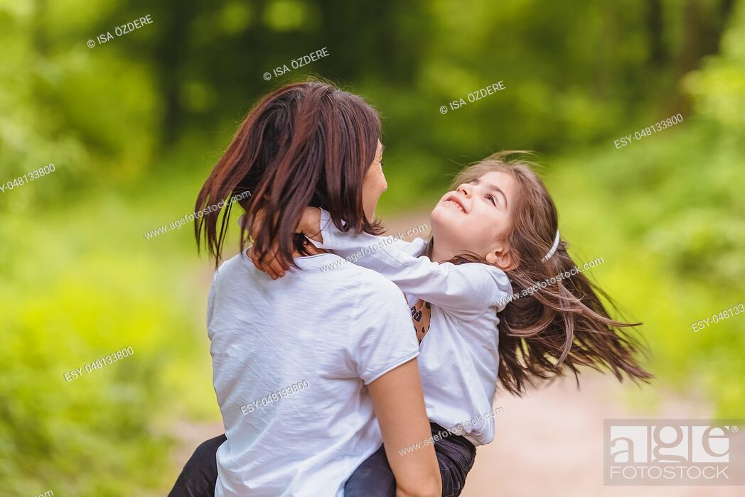 Imagen: Young mom holds and spins her little girl in forest. Happy mother and daughter moments with love and natural emotion. Photo of young mother and her daughter.