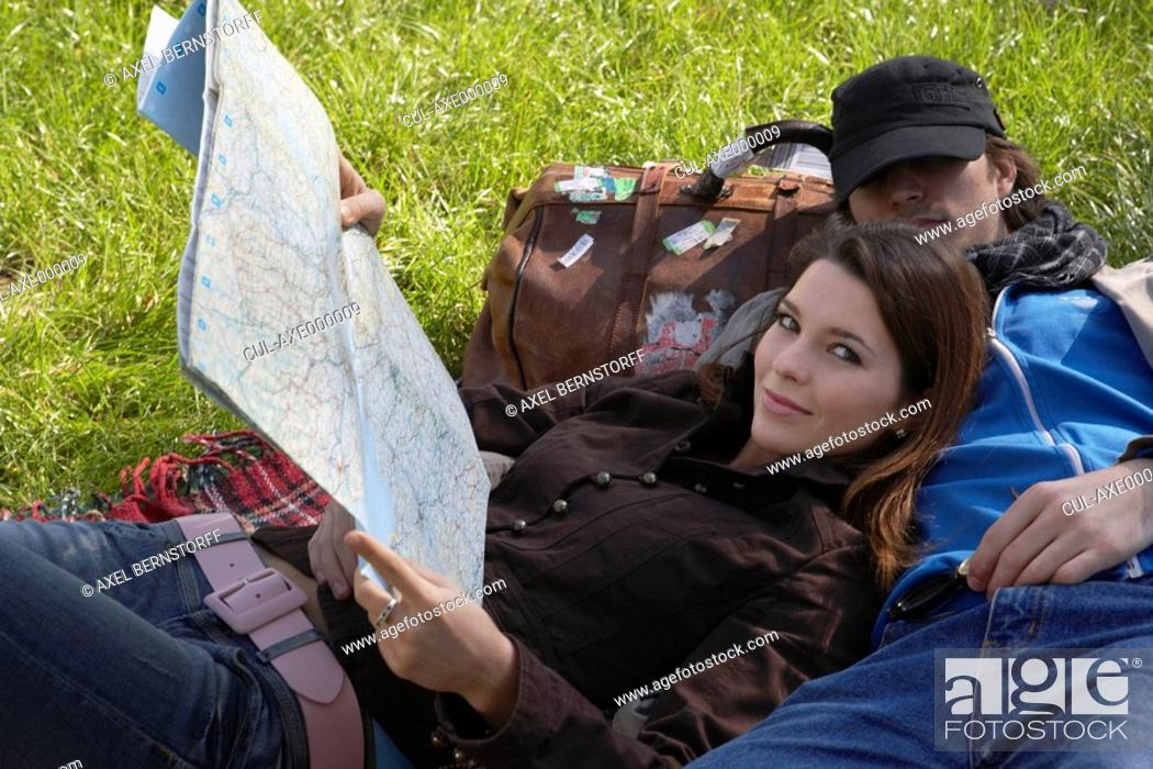 Stock Photo: Woman smiling holding map reclining on sleeping man in a park.