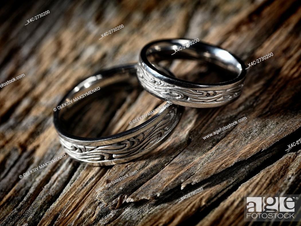 Stock Photo: Two white gold wedding rings with Celtic design on rustic wood background, artistic still life.