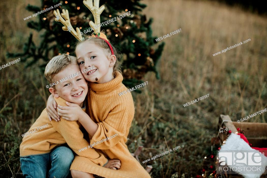 Imagen: Smiling siblings embracing while sitting by Christmas tree on land.