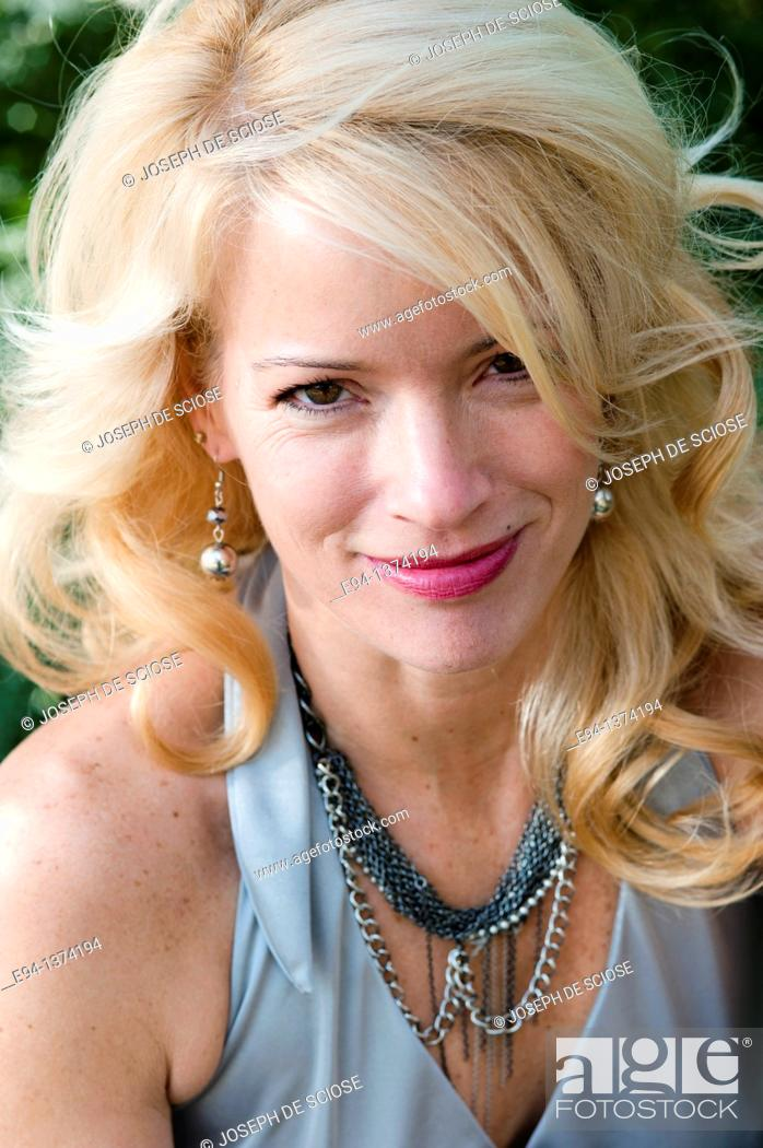 Stock Photo: Portrait of a 44 year old blond woman, outdoors.