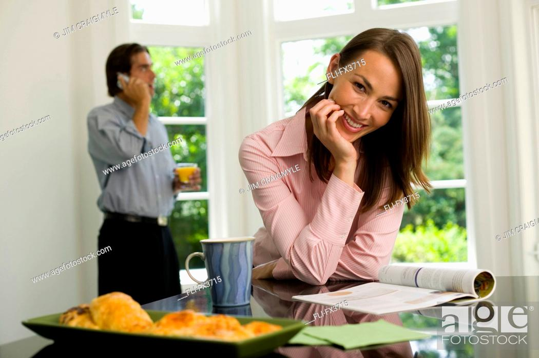 Stock Photo: Woman with Magazine, Man on Cellphone in Kitchen.