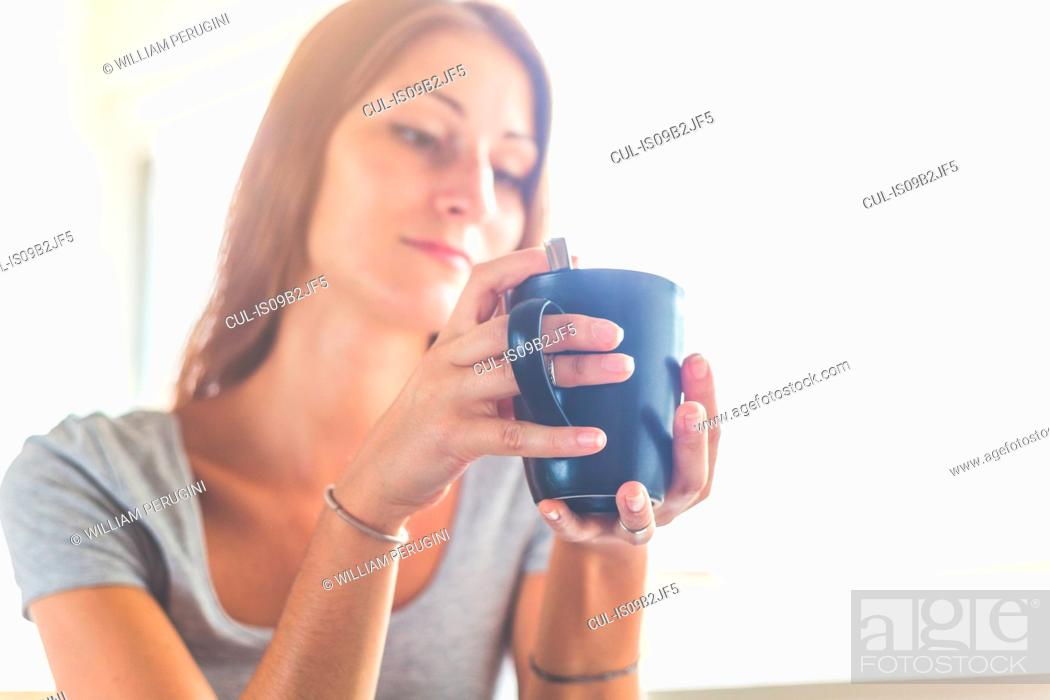 Stock Photo: Woman holding cup looking away.