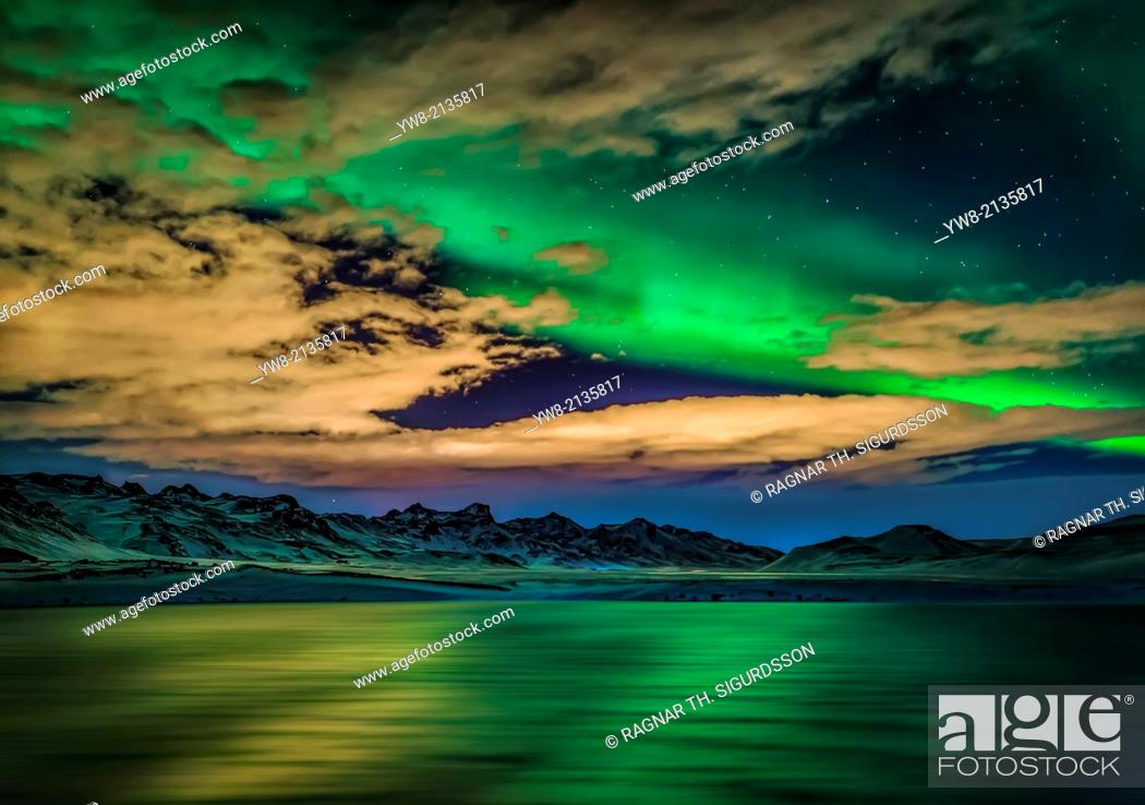 Photo de stock: Aurora Borealis over Lake Kleifarvatn, Iceland. Cloudy evening with northern lights reflecting on the lake.