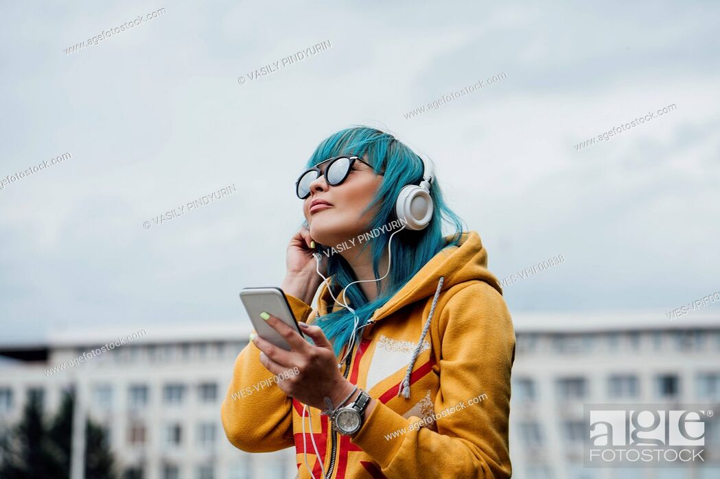 Stock Photo: Portrait of young woman with dyed blue hair listening music with smartphone and headphones.
