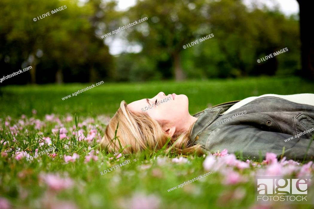 Stock Photo: A young woman lying on the grass in springtime.