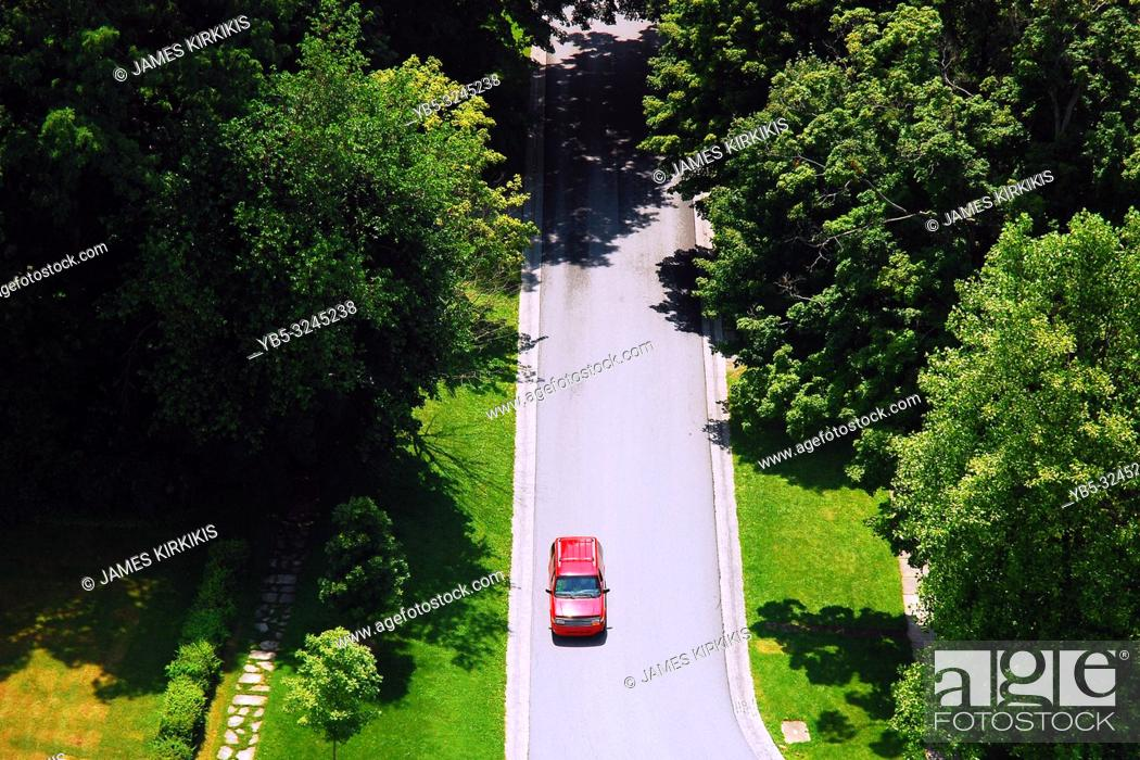Imagen: A car makes its way down a country lane in an aerial view.
