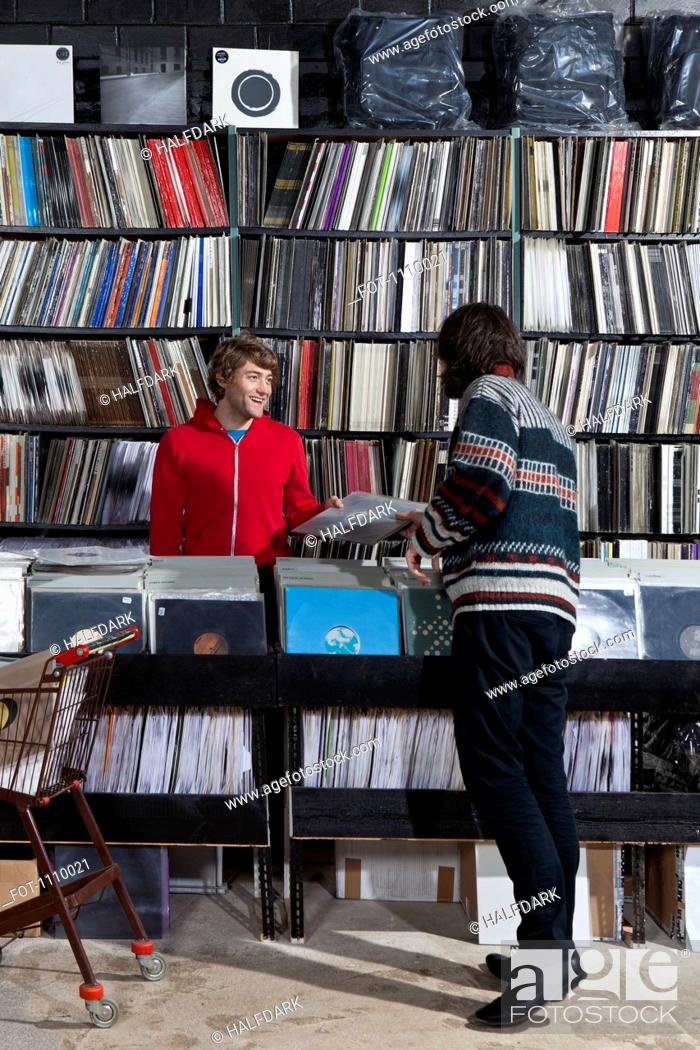 Stock Photo: A sales clerk giving a record to a customer in a record store.