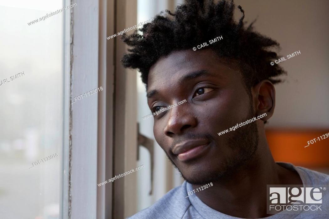 Stock Photo: A young man looking out a window.