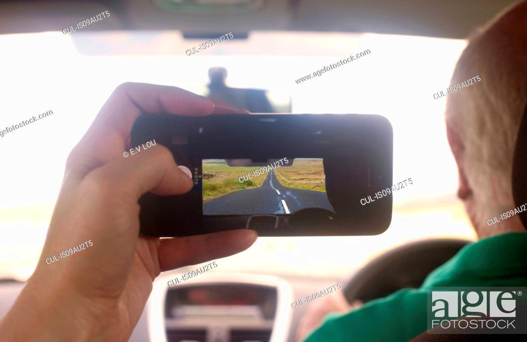 Stock Photo: Womans hand in car photographing diminishing perspective of rural road, Cumbria, UK.