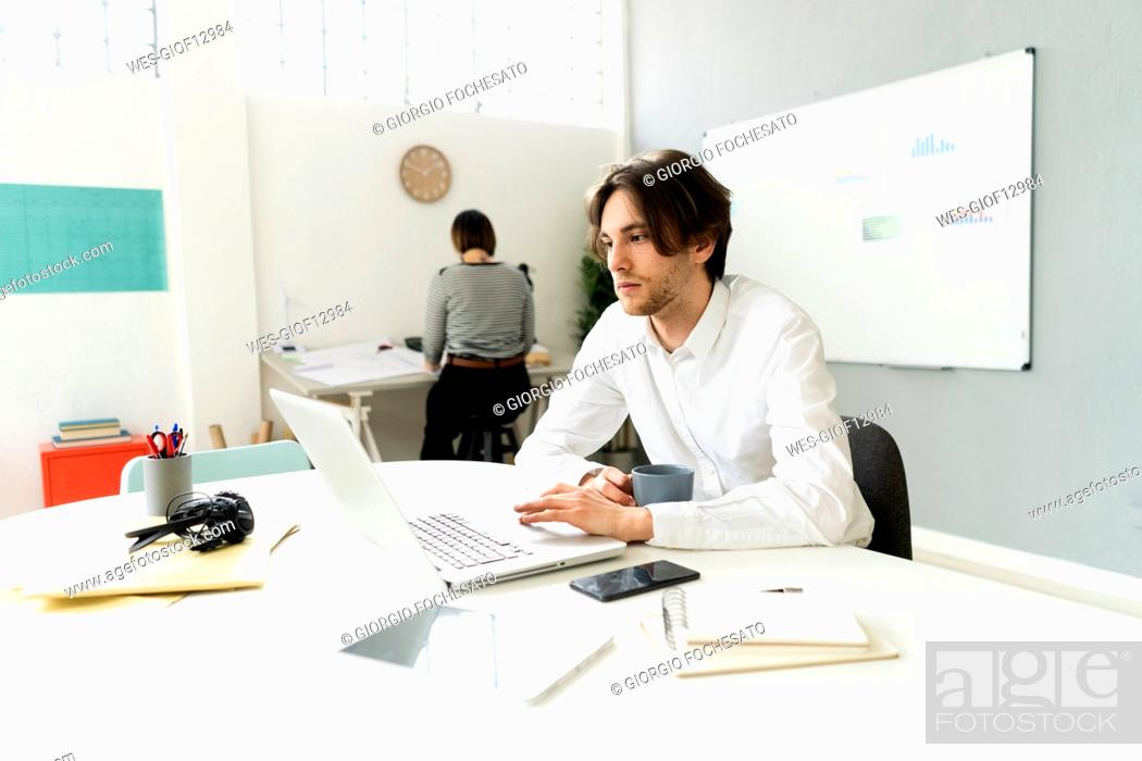 Imagen: Male entrepreneur using laptop while sitting with colleague in background at office.