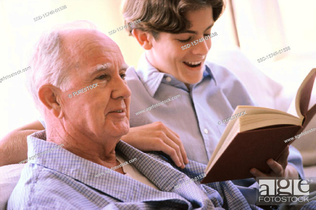 Stock Photo: Teenage boy reading to an elderly man.