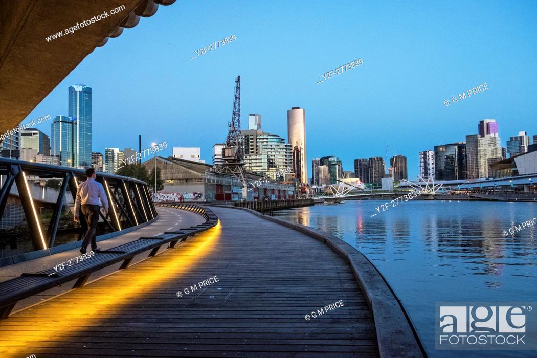 Stock Photo: Man walking along Jim Stynes Bridge, below Wurundjeri Way, with view of Southbank, Melbourne.
