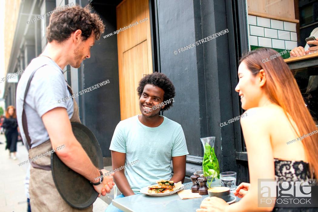 Stock Photo: Waiter serving couple at city sidewalk cafe.