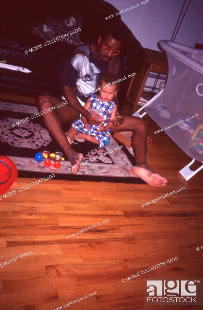 Stock Photo: View of an African American man reading a book to a young African American child, July, 1995. The little girl and man sit together on the floor of a family.