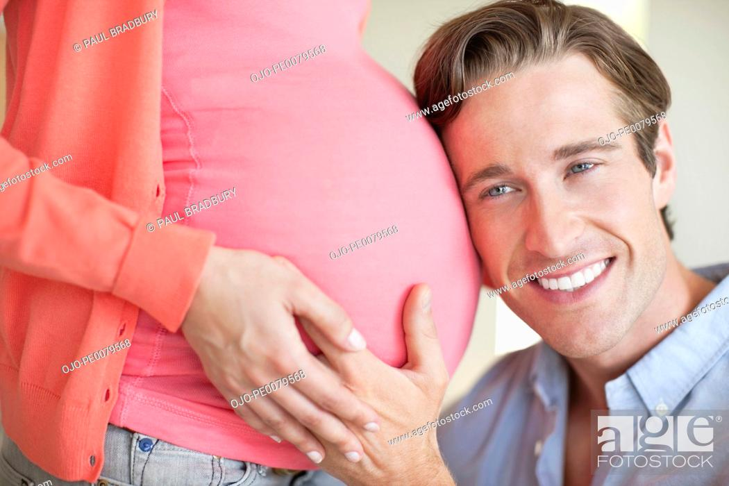 Stock Photo: Husband listening to wife's pregnant stomach.
