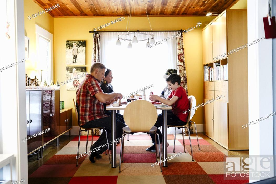 Stock Photo: Side view of dining room with family sitting in table.