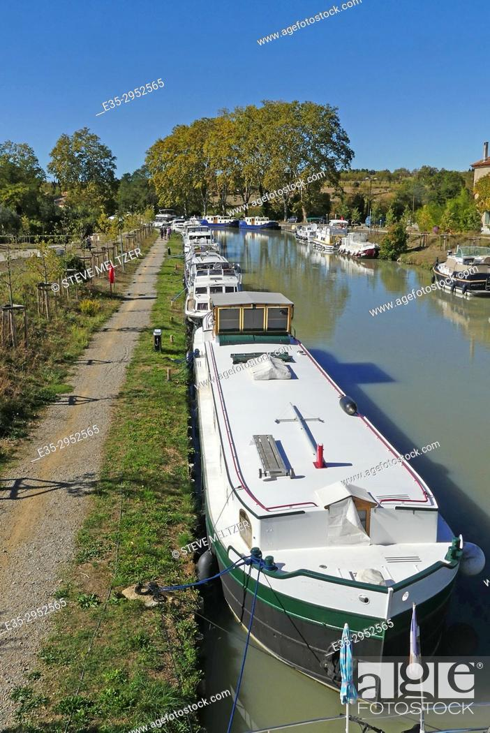 Stock Photo: People on the pedestrian path along the Canal du Midi at Capestang, France.