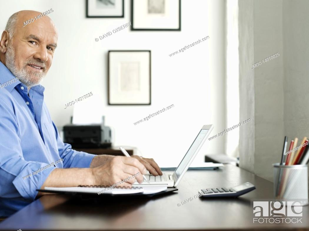 Stock Photo: Middle-aged man sitting at desk using laptop and writing in notepad.