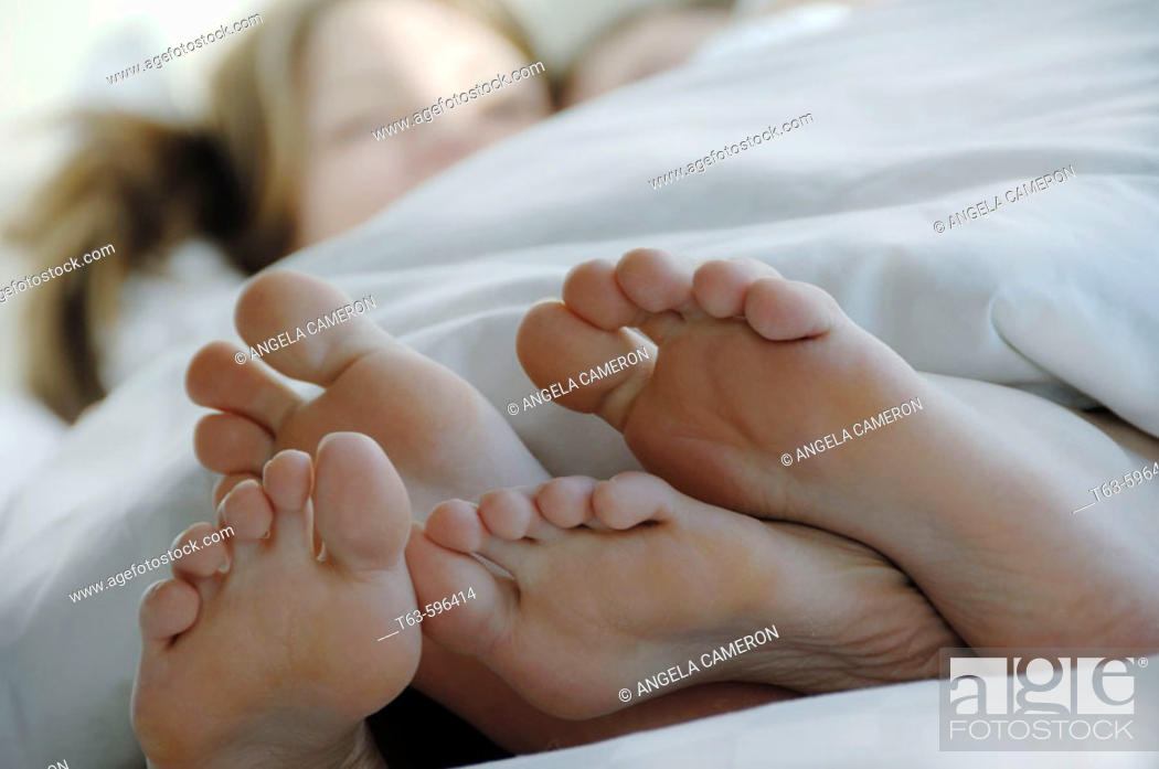 Stock Photo: Young couples laying together in bed with feet in foreground.