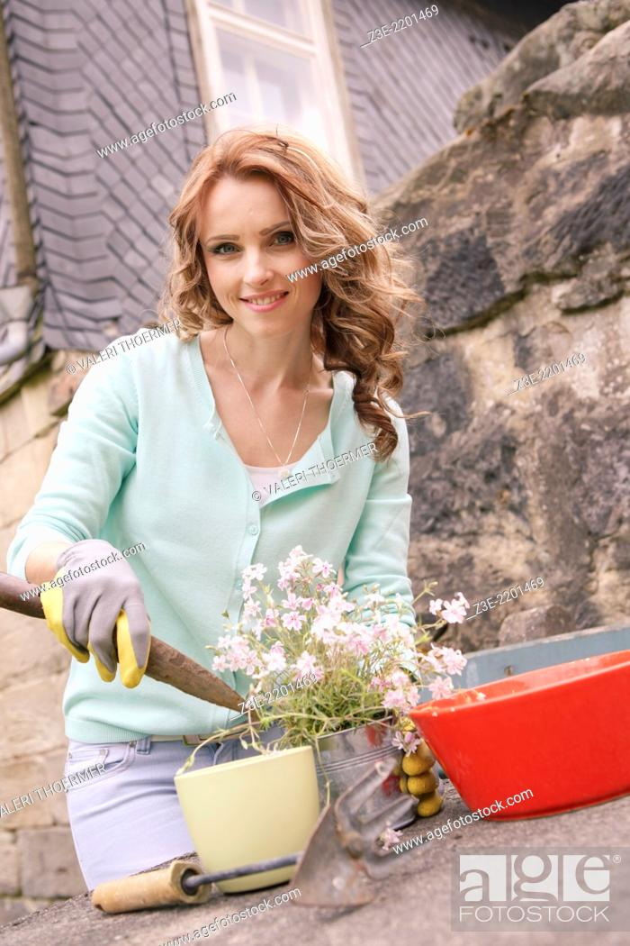 Stock Photo: young woman working in the garden, Coburg, Germany.