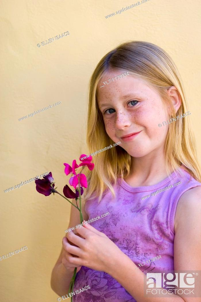 Stock Photo: Portrait of nine-year old blonde blue eyed girl with freckles smiling while holding purple flowers.