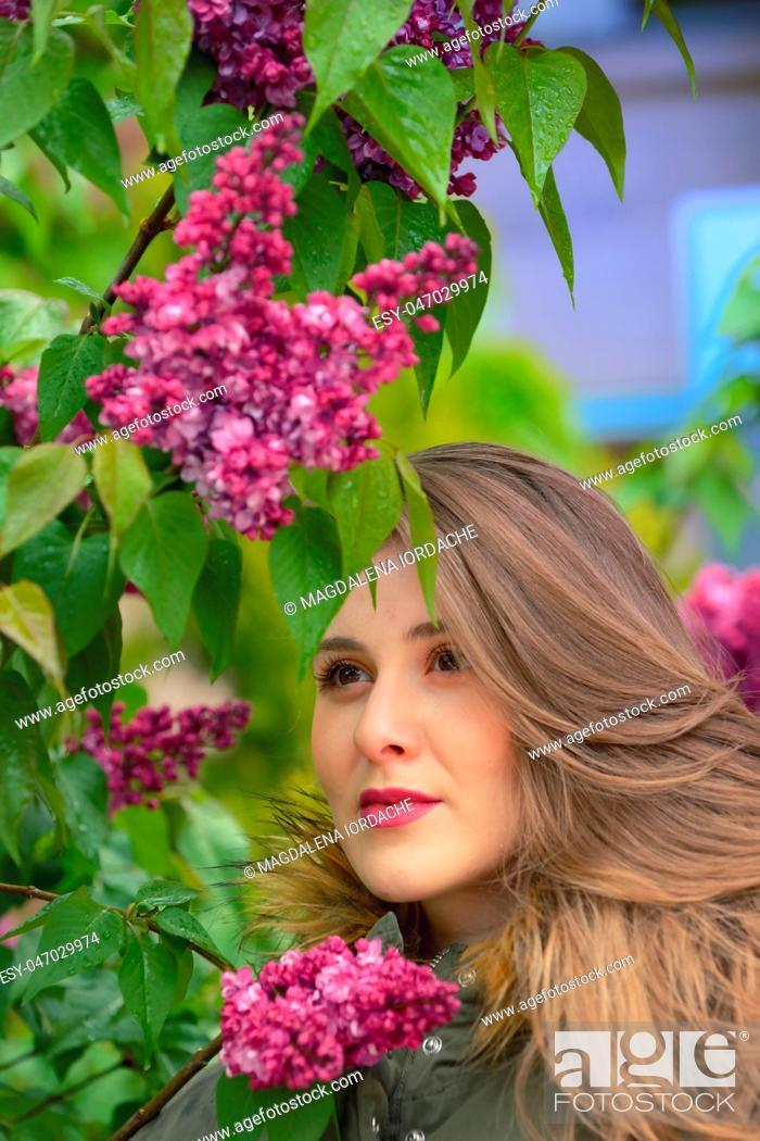 Photo de stock: Young girl posing near lilac bushes in rainy day.