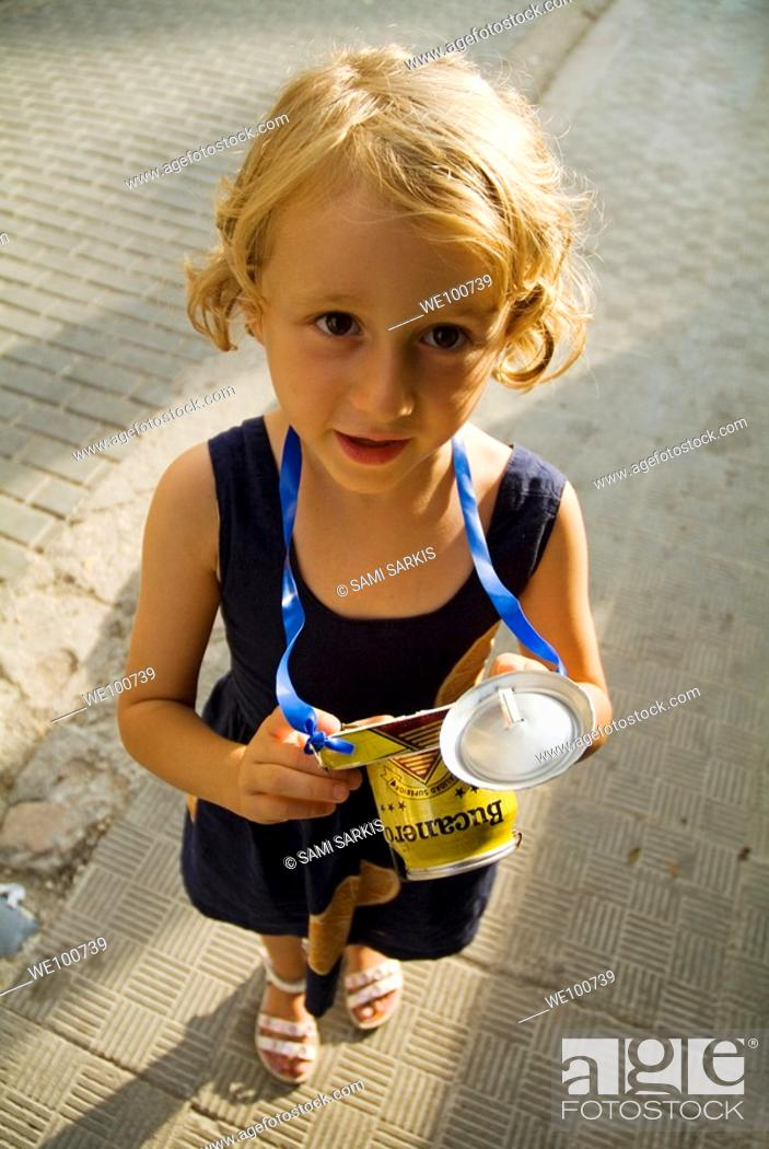 Stock Photo: Little girl playing with a toy camera made from a can, Havana, Cuba.