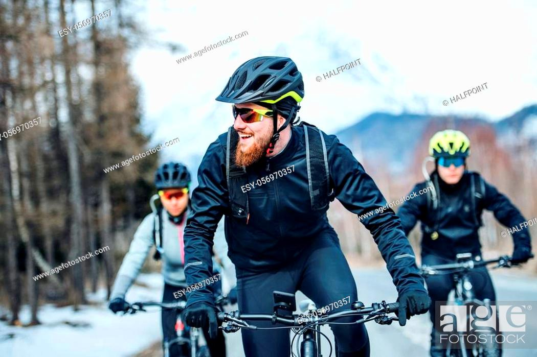 Stock Photo: A front view of group of young mountain bikers riding on road outdoors in winter.