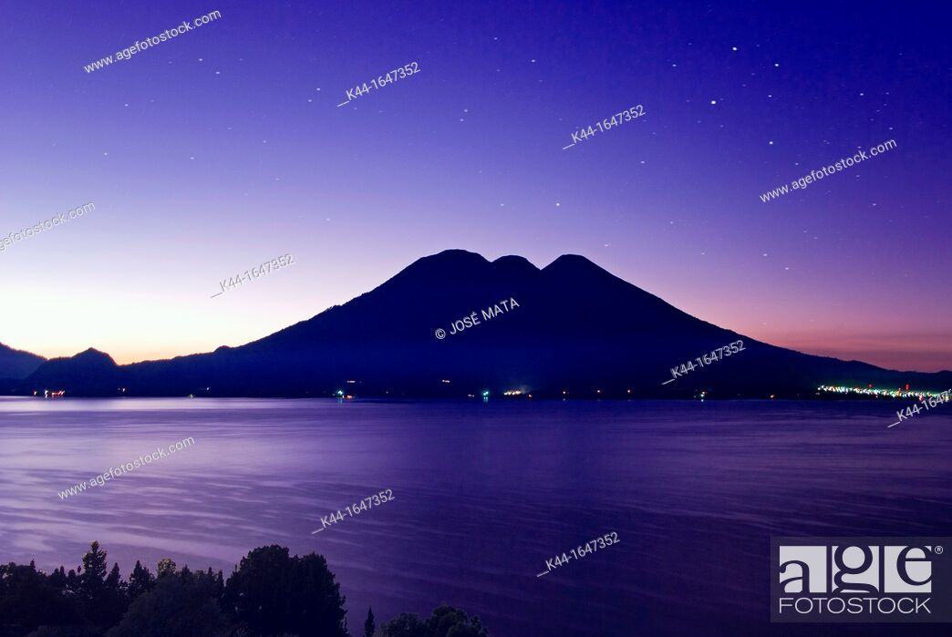 Stock Photo: Sunrise at Lake Atitlán in Guatemala with volcanoes Tolimán and Atitlán in the background.