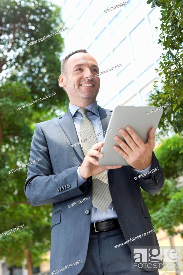 Stock Photo: Germany, Leipzig, Businessman using digital tablet, smiling.