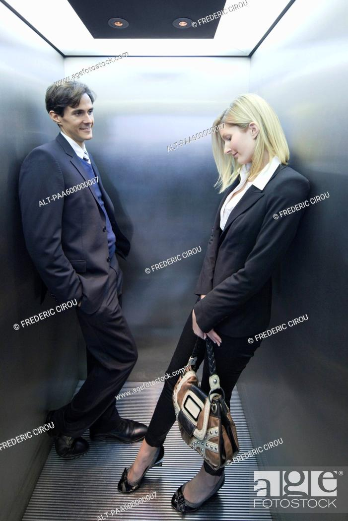 Stock Photo: Colleagues flirting in elevator.
