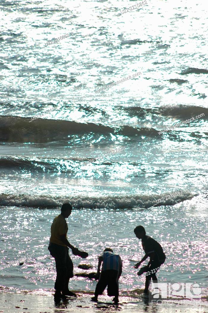 Stock Photo: Anjuna, Goa, India: Indian tourists at the beach.