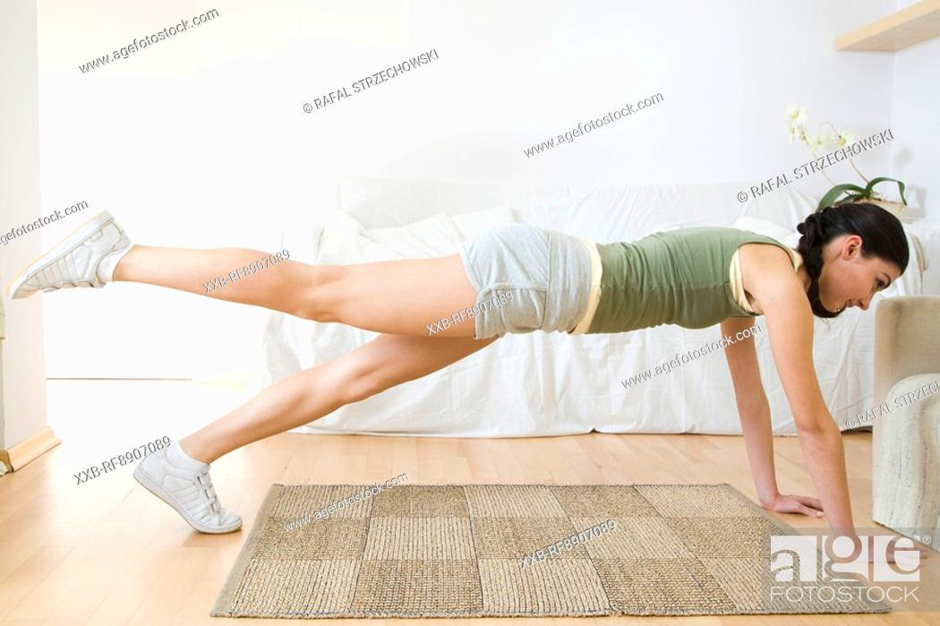 Stock Photo: young woman training at home.
