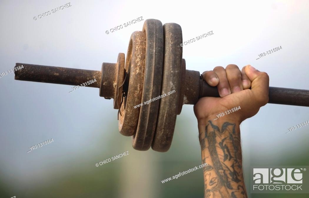 Stock Photo: A Central American migrant traveling across Mexico to work in the United States trains with weights at the Catholic priest Alejandro Solalinde's shelter.