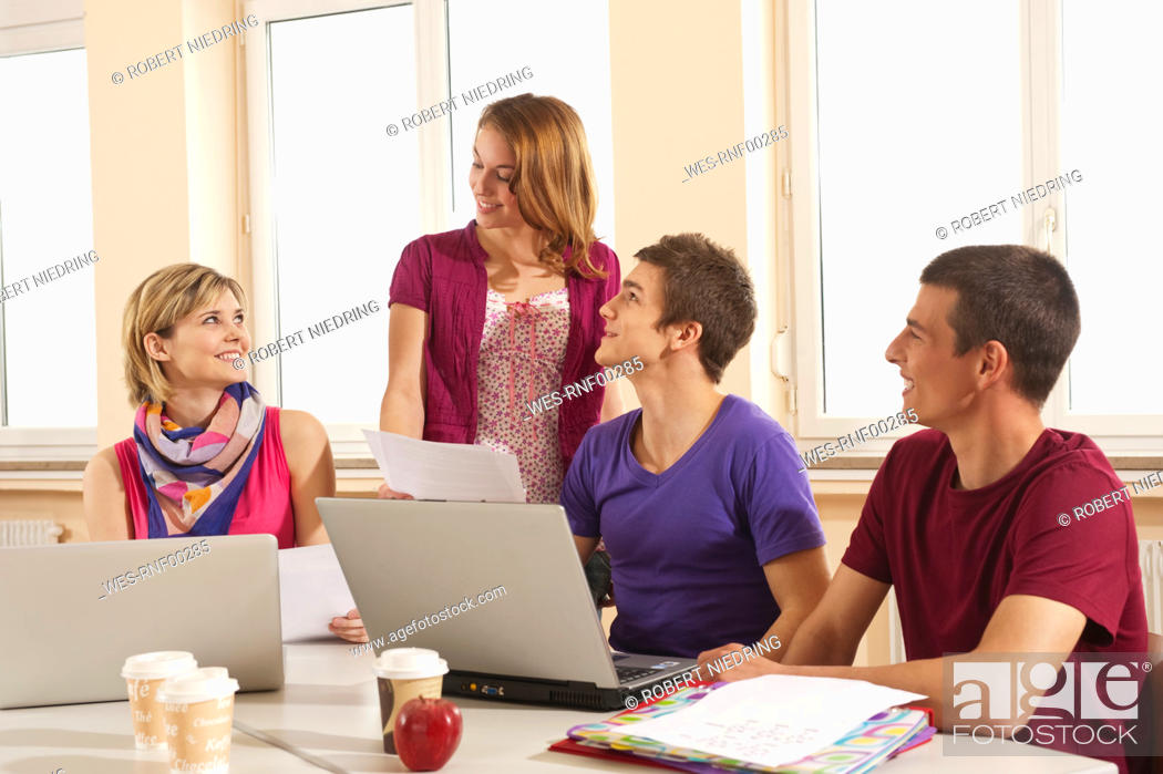 Stock Photo: Germany, Emmering, Students using laptop with disposable cup and apple on table.