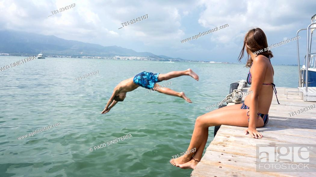 Stock Photo: by jumping boy and girl watching sea, San Carlos de la Rapita, Tarragona.