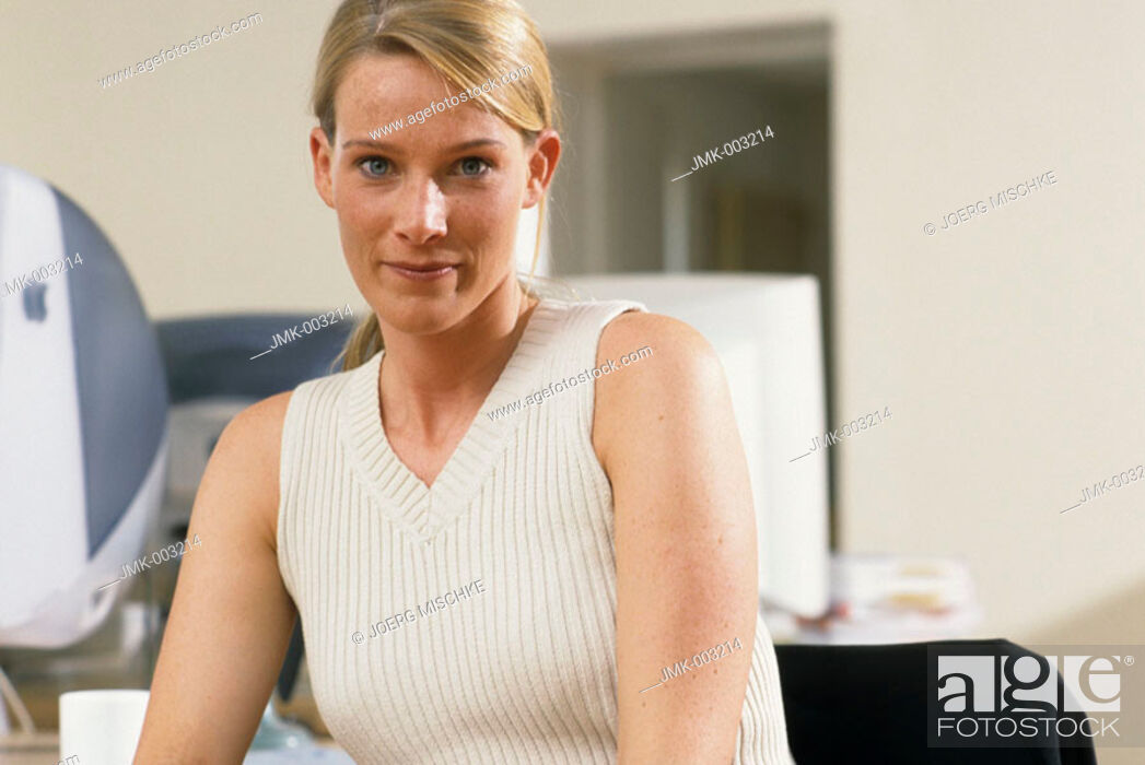 Stock Photo: A young woman, businesswoman, 25-30 30-35 35-40 years old, sitting in an office.