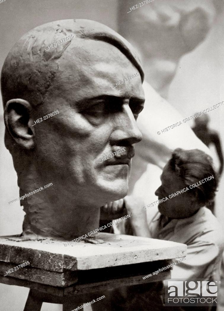 Stock Photo: A sculptor working on a large portrait bust of Adolf Hitler, Germany, 1936. Artistic creative work expressive of the new national spirit.
