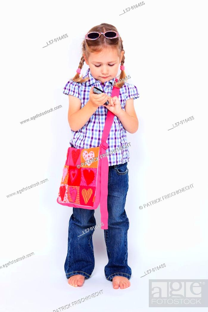 Stock Photo: little girl standing with mobile phone and handbag over shoulder wearing sunglases, Switzerland.