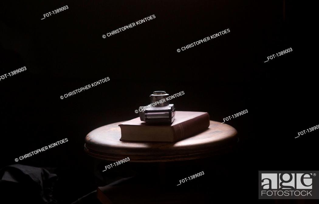 Stock Photo: Camera and book on table against black background.