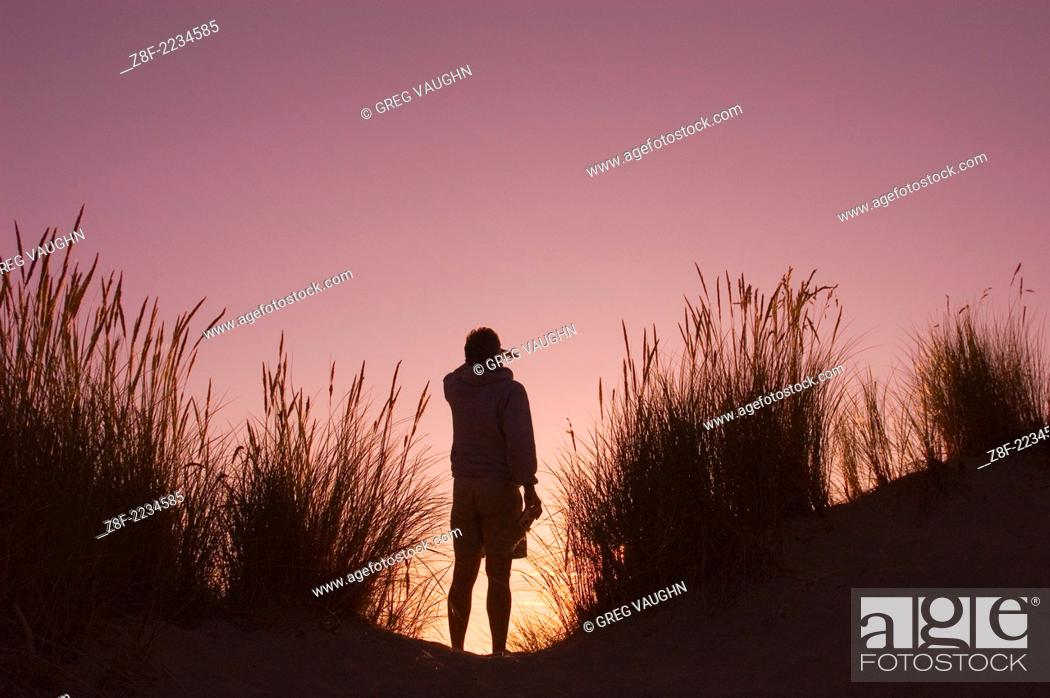 Stock Photo: Man checking the view from the top of the sand dune at sunset; Carter Lake Campground, Oregon Dunes National Recreation Area, Oregon coast.